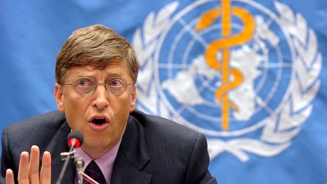 Microsoft-Gründer Bill Gates bei einer Ansprache vor einer Flagge mit WHO-Logo