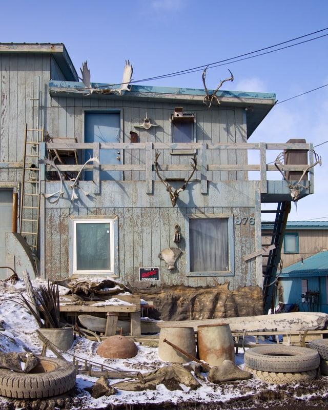 Ein Haus, das vollgehängt ist mit Tierknochen und -geweihen, im Vordergrund Fässer, Autoreifen und allerlei Schrott.