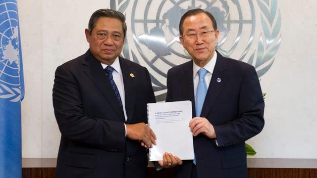 Zwei Männer vor dem UNO-Emblem
