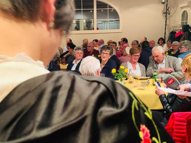 Blick über die Schulter einer Trachtenfrau ins Publikum