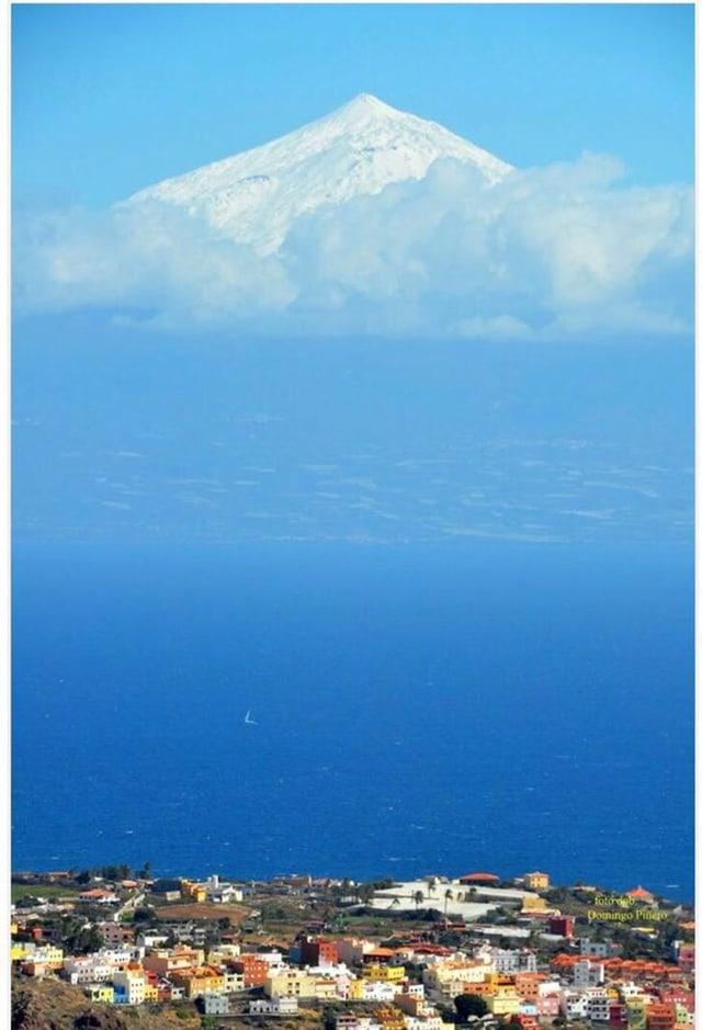 Unten im Bild eine farbige Küstenstadt der Insel Gran Canaria. Dahinter blaues Meer mit einem Segelschiff. Am Horizont ist Teneriffa und über den Wolken der weisse Gipfel des Pico del Teide zu sehen.