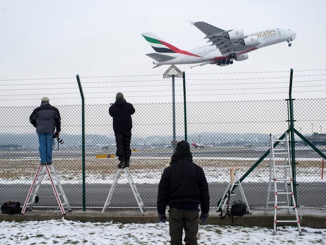 Fotografen am Zaun schauen startendem Flugzeug zu.