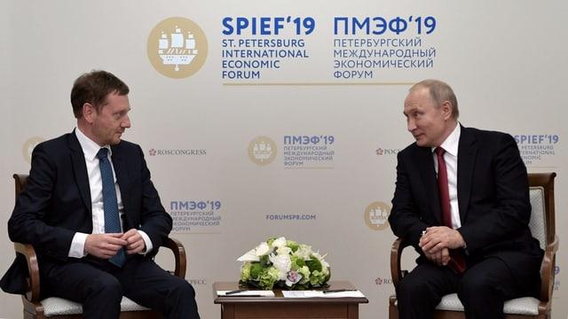Zwei Männer sitzen sich gegenüber. Dahinter eine Schrift: St. Petersburg International Economic Forum.