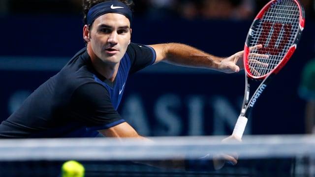 Roger Federer in dunklem Tenue fokussiert einen herannaheneden Ball.