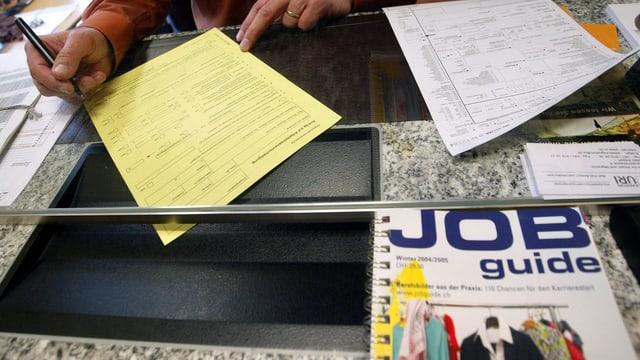 Eine Person am Schalter. Vor dem Schalter ist eine Brochure mit dem Titel «Job Guide»