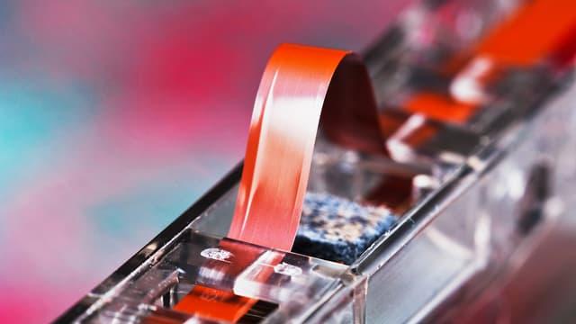 Ein Magnetstreifen, der leicht angehoben aus einer Audio-Kassette schaut.