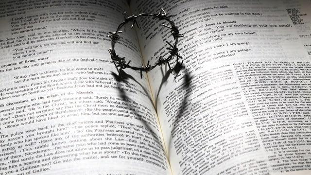 Purtret d'in ritntg da spinatscha mess sin ina bibla uschia che la sumbriva dat in cor.