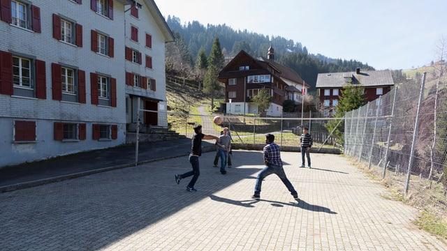 Flüchtlinge spielen vor dem Asylheim Volleyball.