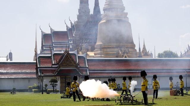 Soldaten in traditioneller Kleidung feuern aus Kanone Schuss ab. Dahinter sieht man Paläste.