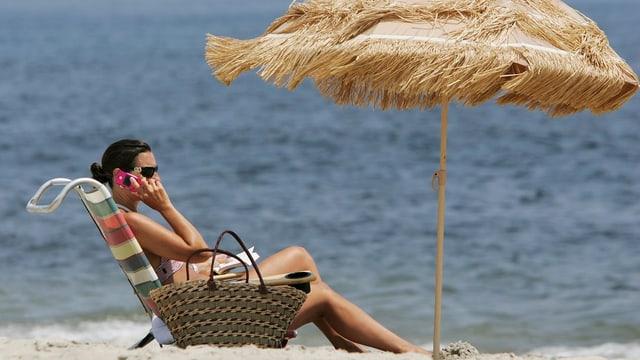 Frau telefoniert am Strand im Liegestuhl unter Strohschirm