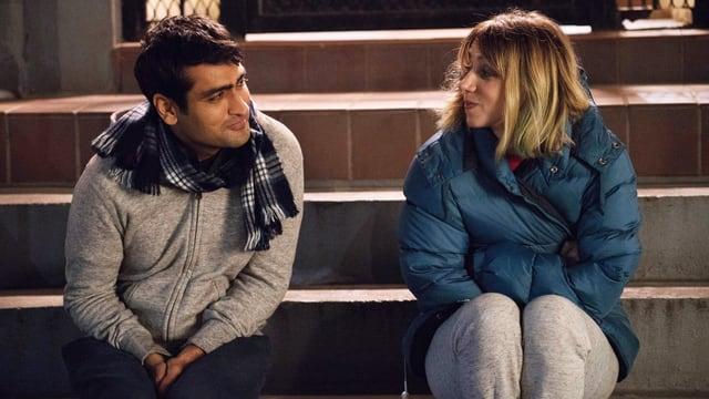 Ein junger Mann und eine junge Frau sitzen auf der Treppe vor einem Hauseingang und schauen sich in die Augen.