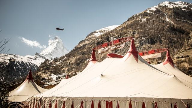 Im Vordergrund ein Zelt, im Hintergrund Berge.