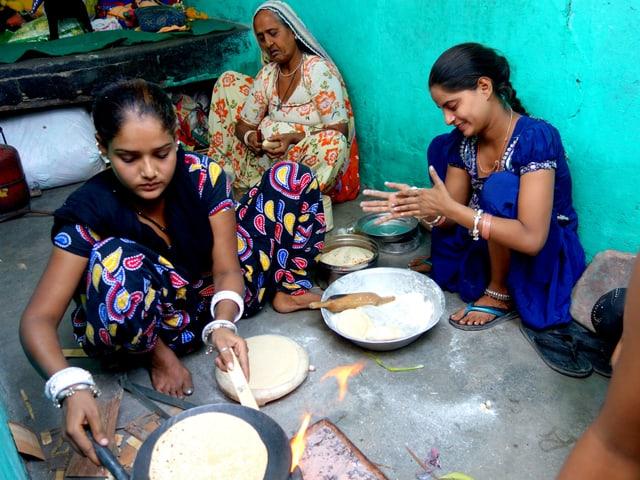 Drei kochende Frauen vor einer türkis Hauswand.