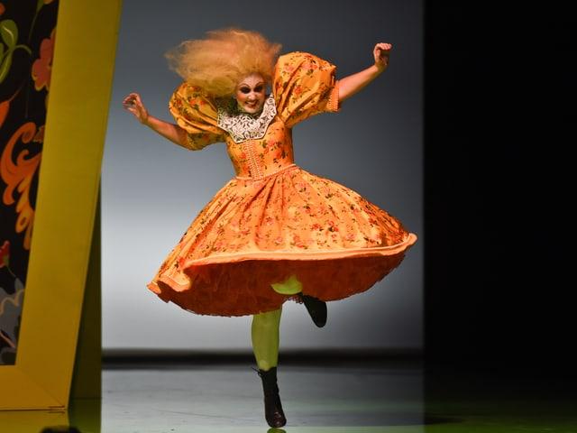 Eine Frau in einem orangen Kleid, knielang, ausgestellt - mit orangen Haaren.