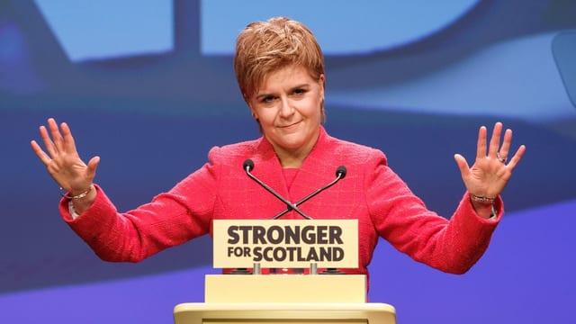 Schottische Premierministerin Nicola Sturgeon hebt vor Rednerpult beide Arme