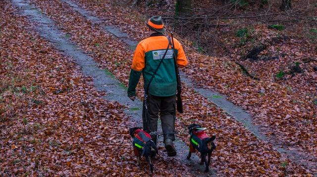 Ein Mann mit zwei Hunden.