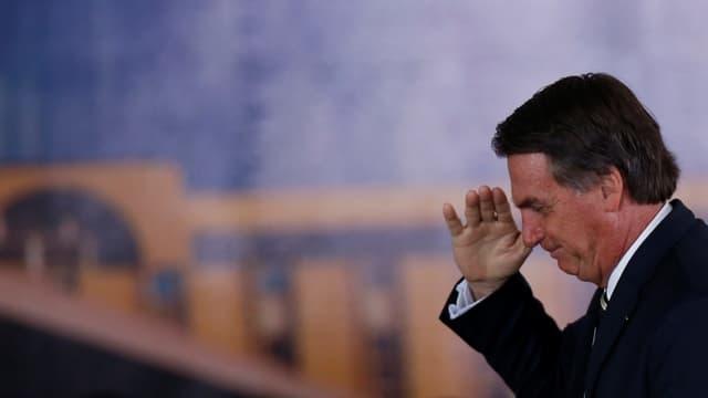 Bolsonaro grüsst mit der Hand am Kopf.