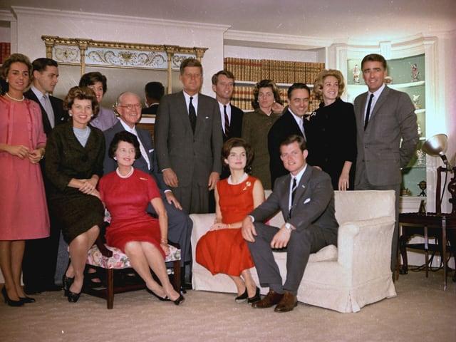 Familienfoto mit Personen, die auf einem Sofa sitzen.