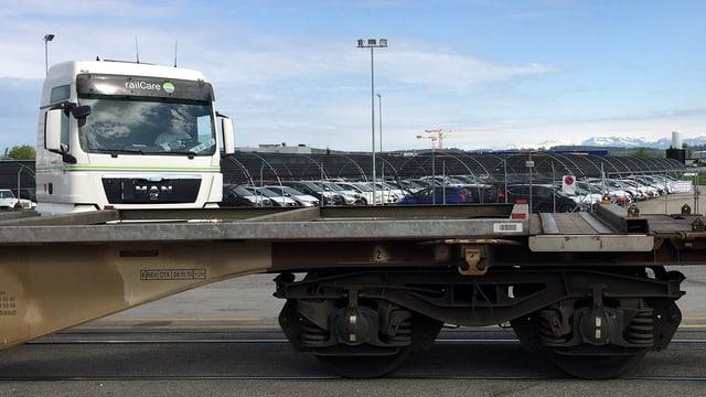 Ein Lastwagen mit Railcare-Schriftzug steht hinter einem leeren Güterwagen der Eisenbahn