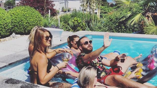 ein junger rapper sitzt mit frauen im swimmingpool