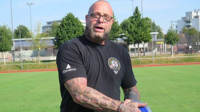 Ein Mann steht mit einem Diskus auf einem Sportplatz.