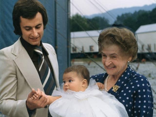 Eine alte Dame mit einem Baby im Taufkleid im Arm, daneben ein Mann im Anzug.