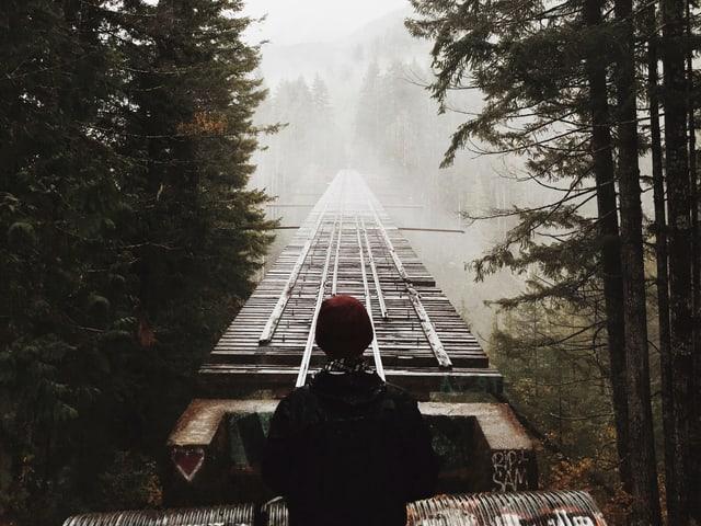 Ein Mann steht in einem nebligen Wald. Ein altes Eisenbahnggleis in die Weite, das aber direkt vor dem Mann abgebrochen ist.