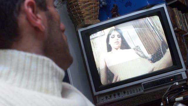Ein Mann schaut sich einen Porno im TV an.
