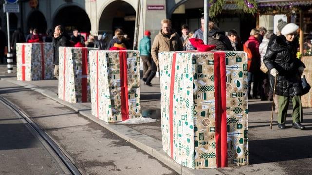 Als Geschenk verpackte Betonelemente stehen auf dem Trottoir. Eine alte Frau mit Stock geht daran vorbei.