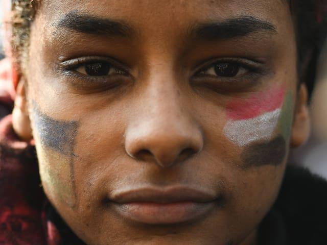 Frau mit aufgemalter sudanesischer Flagge auf der Wange