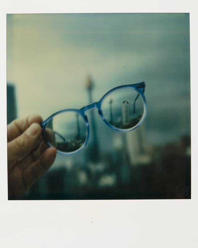 Durch die Brillengläser sieht man die verschwommene Skyline einer Stadt.