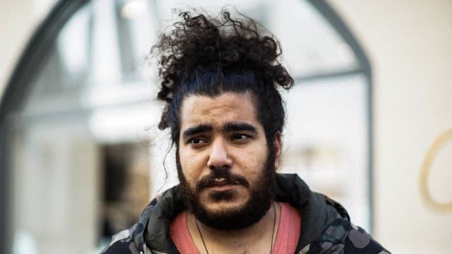 ein bärtiger junger rapper schaut melancholisch böse neben die kamera