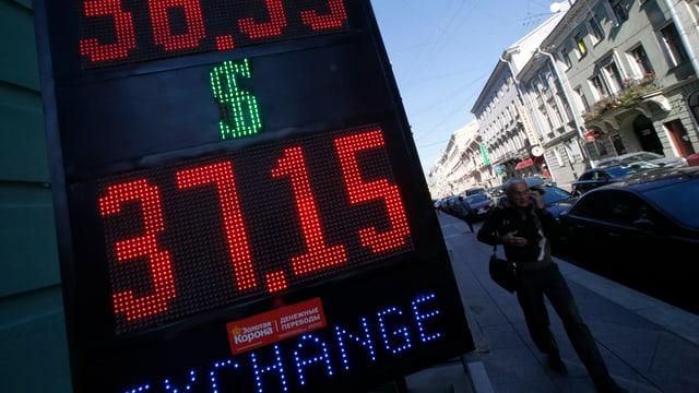 Ein Mann geht an einer leuchttafel mit Wechselkursen vorbei.