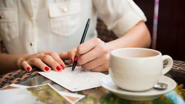 Hinter einer Kaffeetasse sieht man die Hände einer Frau, während sie eine Karte schreibt.