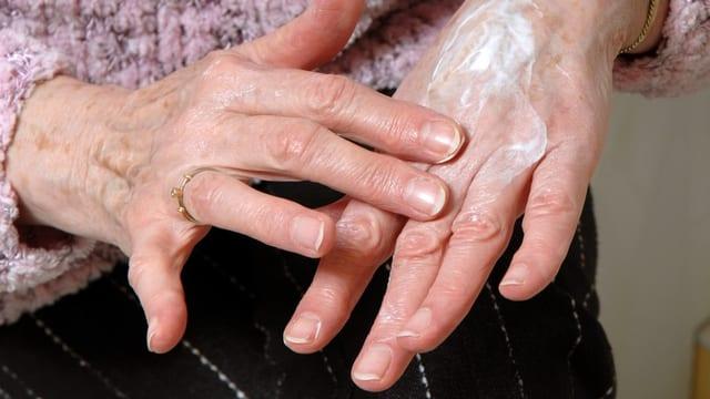 Ein Frau schmiert sich Handcreme auf die Hand