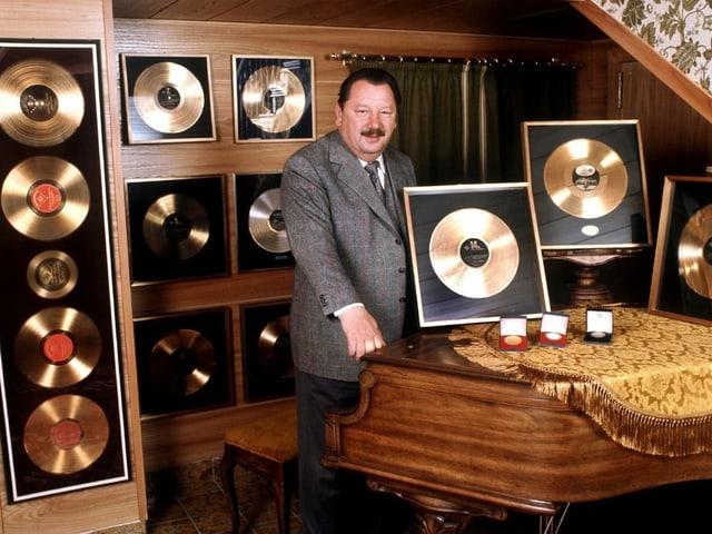 Ein Mann steht in einem Raum voller Goldener Schallplatten vor einem Flügel.