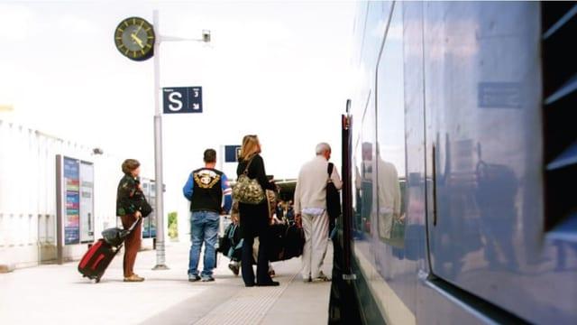 Menschen mit Gepäck steigen in einen modernen Zug ein