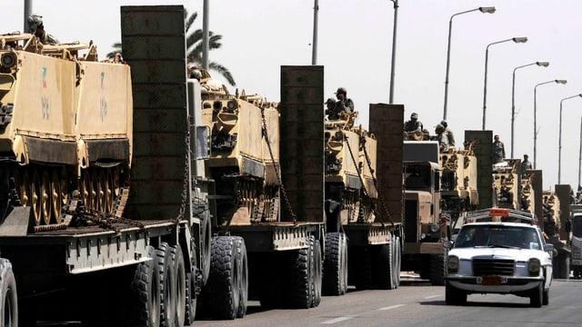 Eine Kolonne Lastwagen transportiert Panzer.