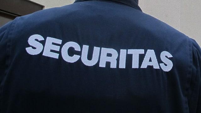 Rückenansicht eines Securitas-Mitarbeiters, auf dem Rücken seiner Uniform ist das Firmenlogo zu sehen.