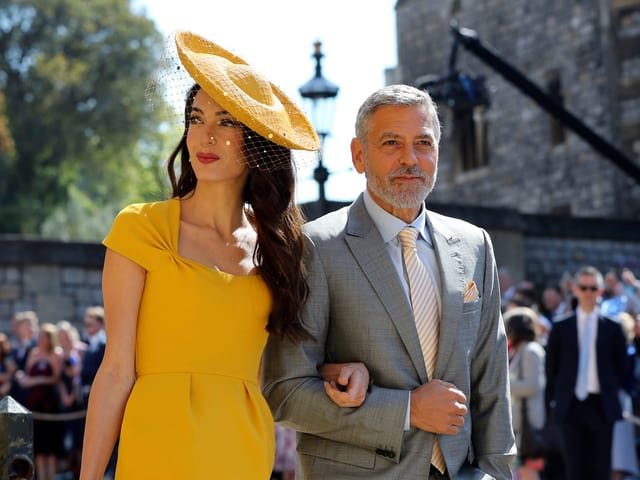 Frau in gelbem Kleid und Mann in grauem Anzug.