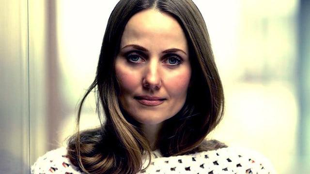 Porträt einer Frau mit langem Haar und weissem Pullover.