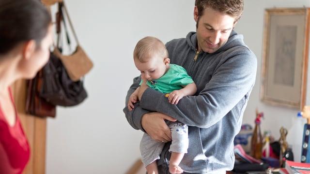 Ein Vater hält ein sechs Monate altes Kind in den Armen, die Mutter steht daneben.