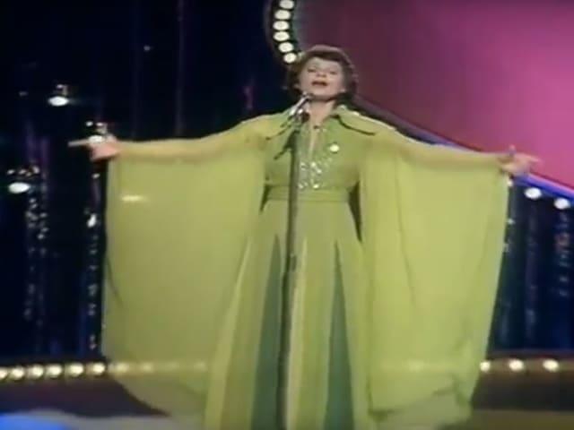 Frau mit wallendem, grünen Kleid. auf Bühne.