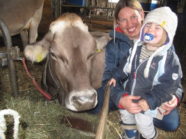 Eine Frau und ein kleines Mädchen stehen im Stroh neben einer Kuh.