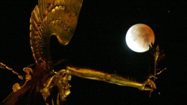 Der Mond während einer Mondfinsternis im Hintergrund des Friedensengels in München.