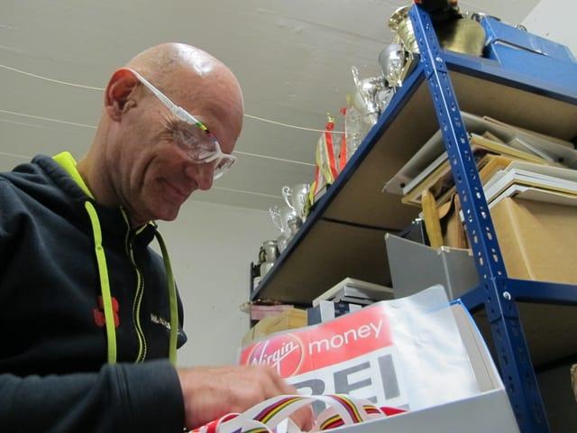 Heinz Frei wühlt in einer Schachtel mit Medaillen.