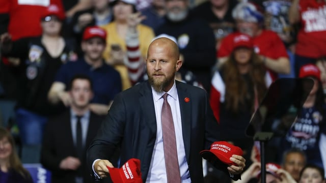 Mann an Wahlkampf mit roten Hüten in der Hand