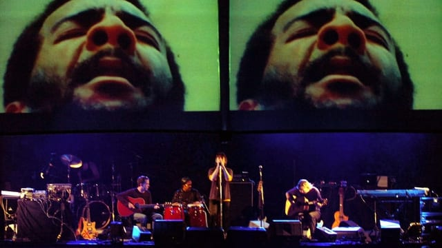 Ein Sänger auf einer Bühne, darüber Bildschirme mit einer Grossaufnahme von einem schwarzen Sänger.