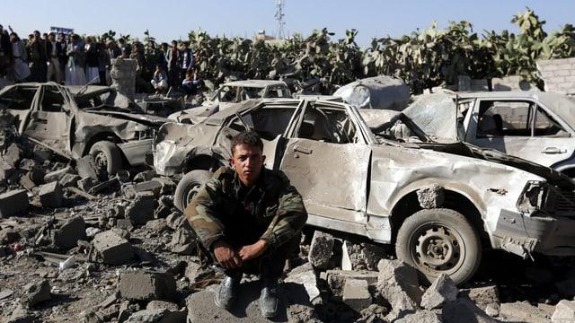 Ein Jemenite sitzt auf einem Steinhaufen vor verbeulten Autowracks.