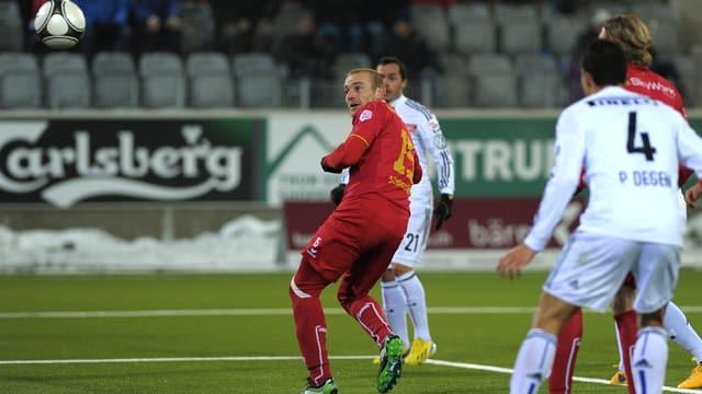 Marco Schneuwly bei einem Kopfball flankiert von Basler Spielern.